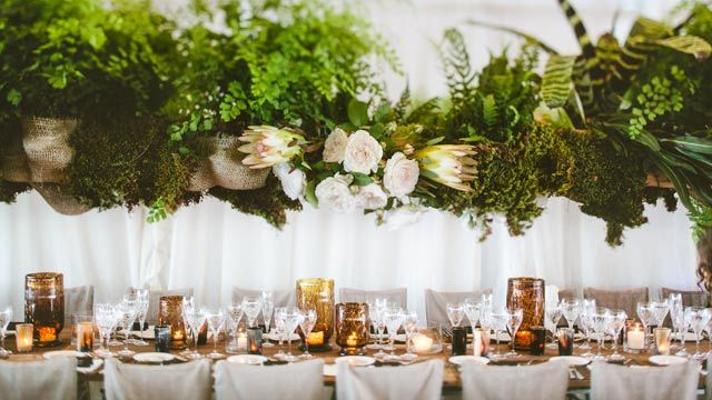 The reception marquee featured timber beams trailing a mass of green foliage, studded with proteas — a flower native to the bride's home in South Africa.