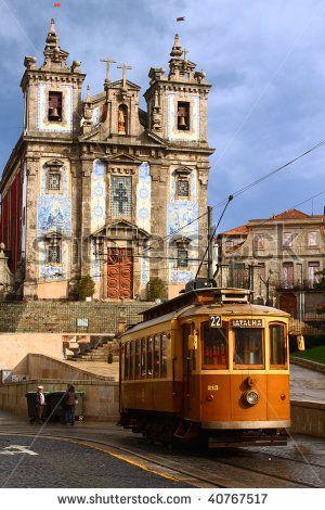 Old-fashioned streetcar ride near church in Porto streets in Portugal, sentimental photo.