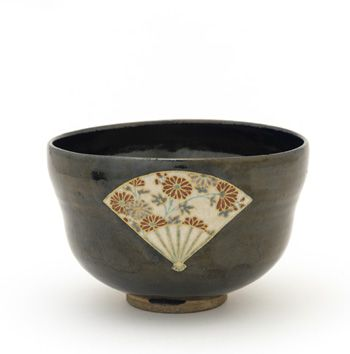 """Tea bowl with reserve design of fans mid-17th century Nonomura Ninsei , (Japanese, active ca. 1646-77) Edo period Stoneware with black glaze and enamels over white glaze W: 5.2 cm Kyoto, Japan. Ninsei used fine-pointed tongs that left nearly invisible scars in the glaze. Moreover, his black glaze serves as a ground for two fan-shaped """"windows"""" of white glaze that he decorated with floral motifs rendered in enamels."""