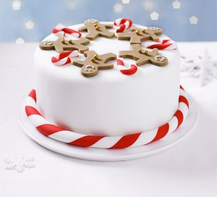 Follow our step-by-step guide to icing a fruitcake with white fondant and marzipan, then decorate with smiling gingerbread men and cute candy canes