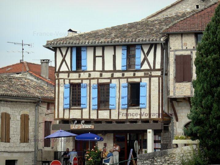 Montaigu-de-Quercy : Terrasse de café et façade à pans de bois d'une maison du village