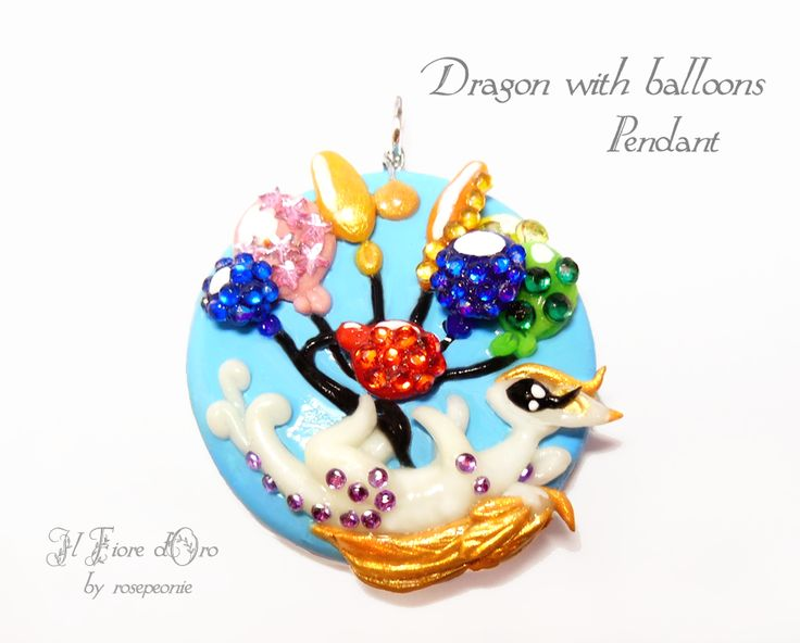 """Dragon with balloons"", pendant with a little white dragon playing in the sky with coloured balloons.  Made in low relief, entirely by hand from molding to painting. On the balloons there many coloured rhinestones (round and star-shaped), which shine and give life to the jewel. This is the ideal..."