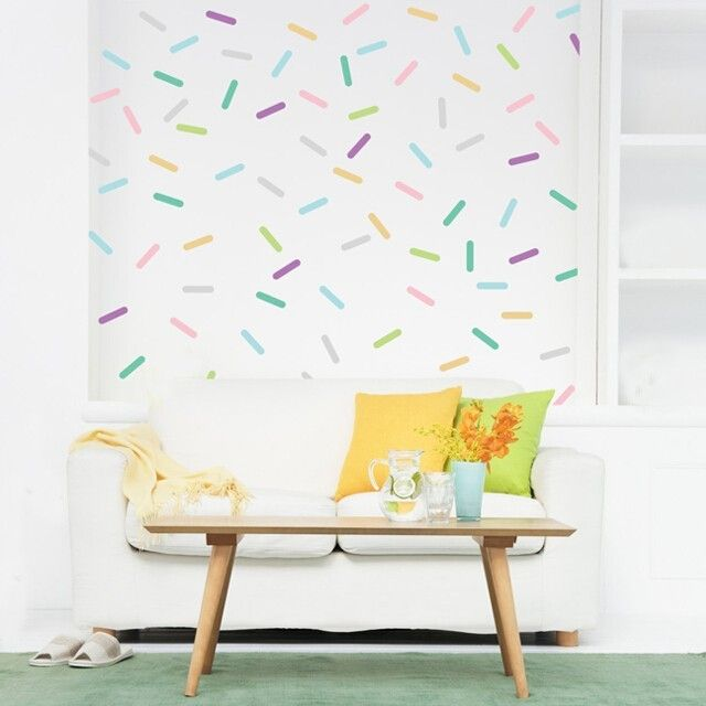 A variety of pastel colored sprinkle wall stickers on a white wall, evenly spaced as to create the appearance of wallpaper. The different colors include soft pink, lilac, light grey, mint, baby blue, key lime, and maize.