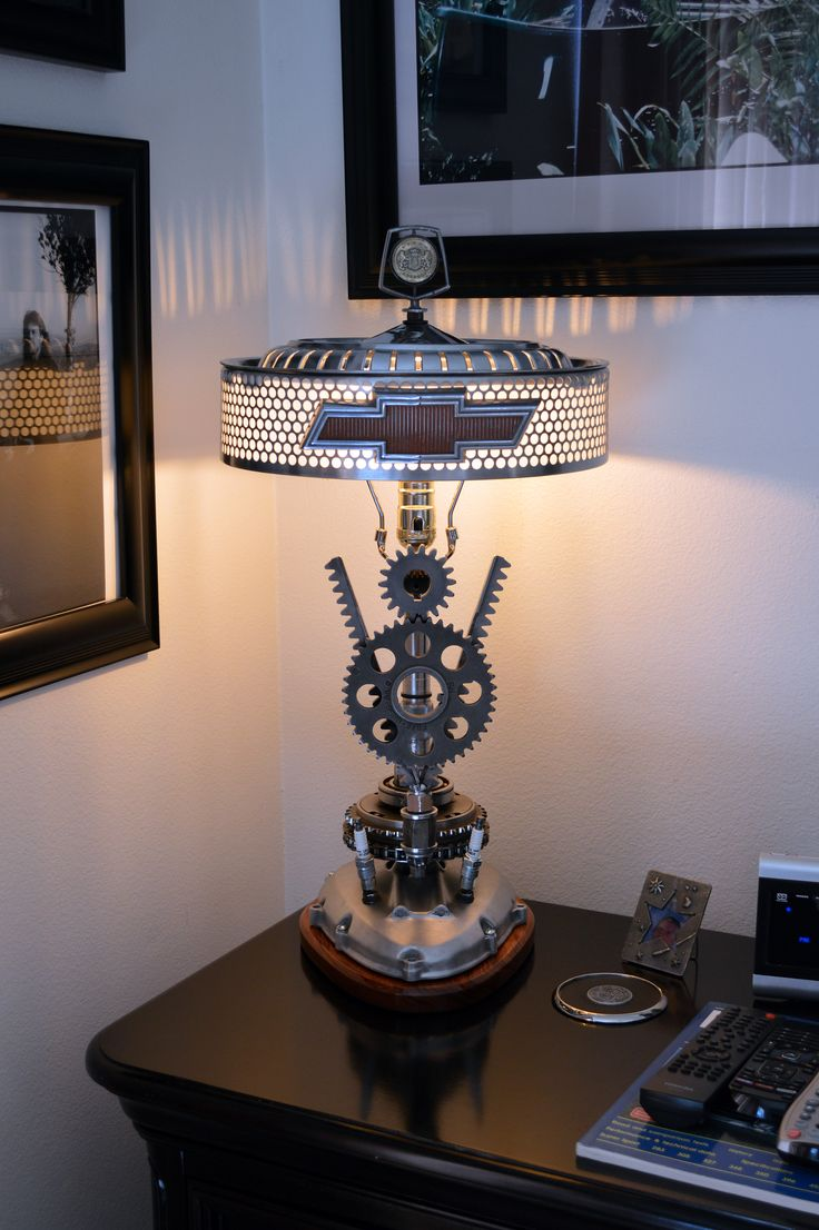 V8 theme lamp. Uses timing gears, power chair parts, and some motorcycle parts as well as spark plugs. Shade is made from mid 60's Plymouth hubcap, with Mercedes air cleaner mesh, 60's Chevy emblem and 77 Chrysler Cordoba hood ornament finial. Base is 70's motorcycle trans cover over Bubinga wood. 120V light socket with LED Edison style bulb.