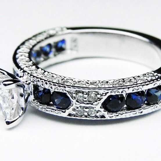 Platinum ring with round cut sapphires and side channel diamonds, with one large antique cushion diamond mounted on top.