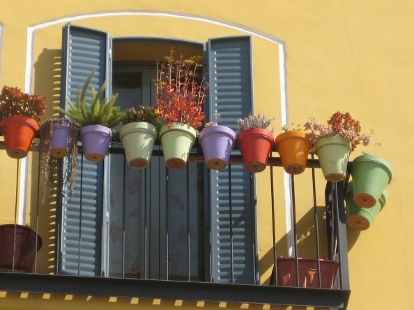 Farvestrålende altan med farverige blomster potter.