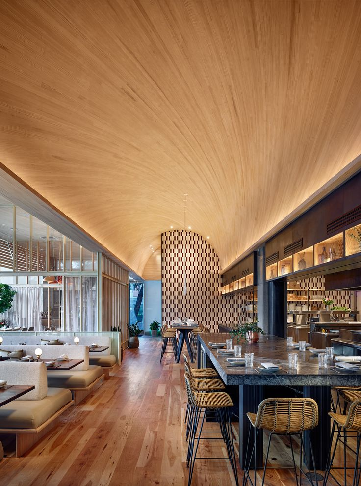 Michael Hsu Office of Architecture has designed a curved wood ceiling for a restaurant in Texas, complete with a large glazed wall and an open kitchen.