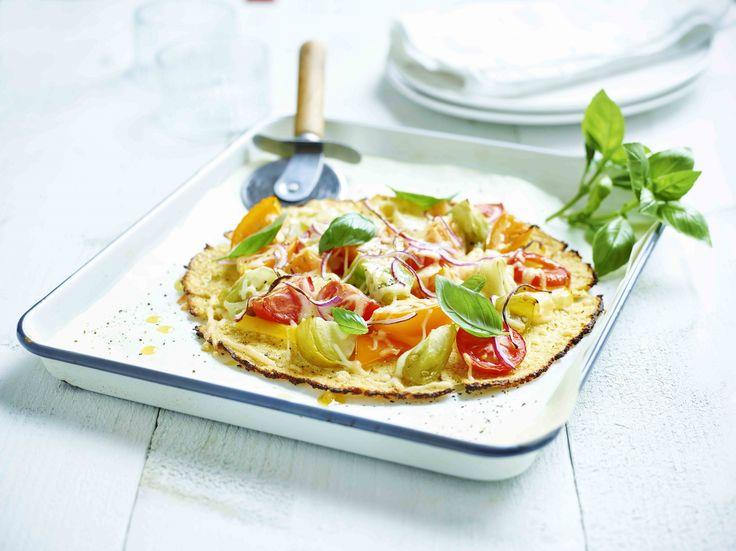 Een overheerlijke bloemkoolpizza met gekleurde tomaten, die maak je met dit recept. Smakelijk!