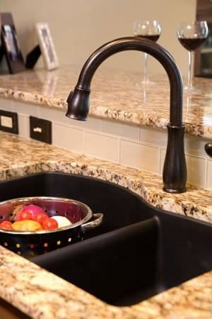 Oil rubbed bronze kitchen faucet and under mount sink complete this kitchen remodel