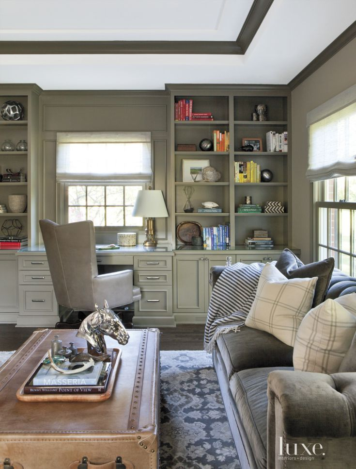 Existing cabinets in the office were painted in Benjamin Moore's Texas Leather. A charcoal velvet sofa by Hickory Chair joins a Four Hands vin- tage trunk; the leather chair is by Hancock & Moore. A wool carpet by Masland Carpets & Rugs grounds the space.