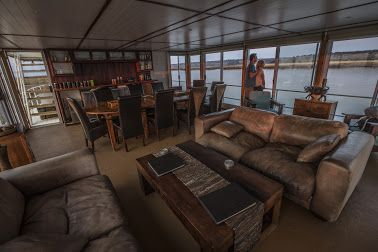 The middle deck: You will find the main living area comprising of a lounge and dining area. The lounge is perfect for relaxing by offering comfortable leather sofas and single chairs. The informative library offers a variety of books that will help enhance your safari experience.