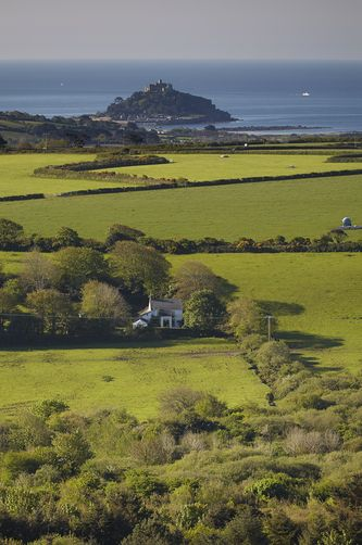 St Michael's Mount, seen across farmland from Trencrom Hill, near St Ives, Cornwall.                                                                                                                                                      More