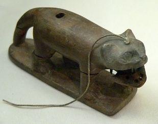 Gato de juguete de madera. Tebas, Egipto. Con mandíbulas móviles y dientes de bronce. Data de la época del Imperio Nuevo, 1550-1070 aC
