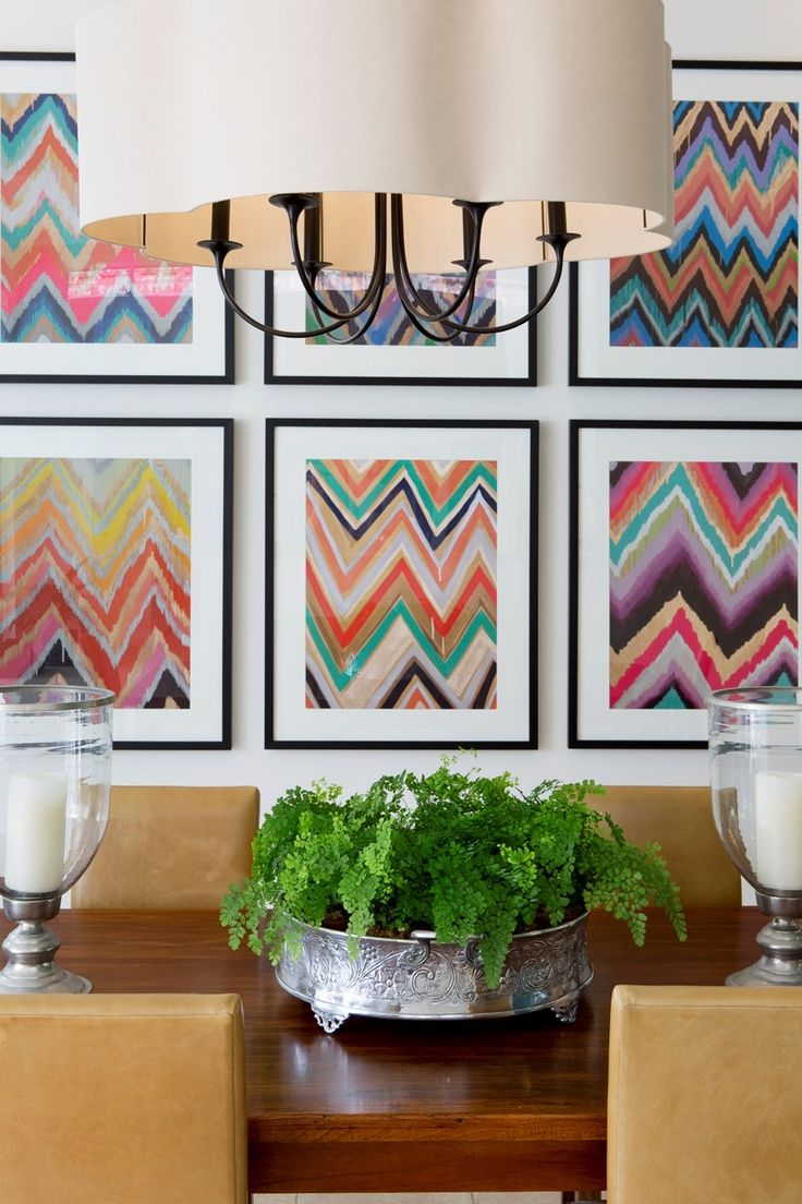 This dining room features a spectacular decorative pendant with 6 large-scale brightly coloured abstract prints.