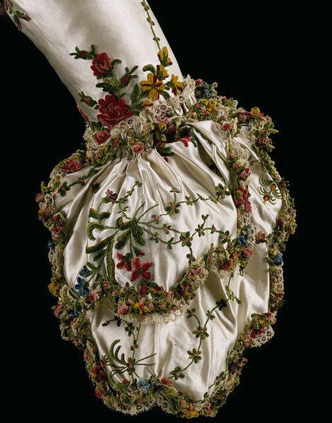 Mantua 1775-1785. The tangled garden of chenille decoration on this court mantua enhances the white silk satin fabric.