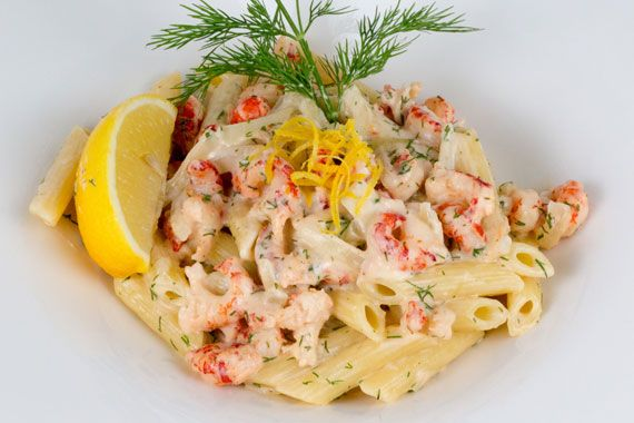 A dish of pasta with crayfish tails garnished with lemon and dill