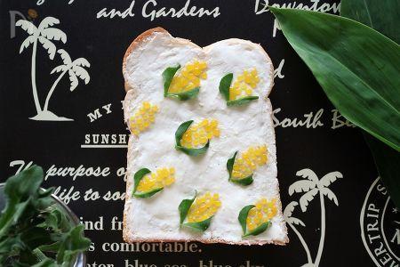 食パンにクリームチーズを塗って真っ白いキャンバスに。そこにマンゴージャムを点々と絞ってとうもろこしを描き、アイスプラントで葉っぱに見立ててみました。  丸をたくさん絞るだけでかわいいとうもろこしの完成です!