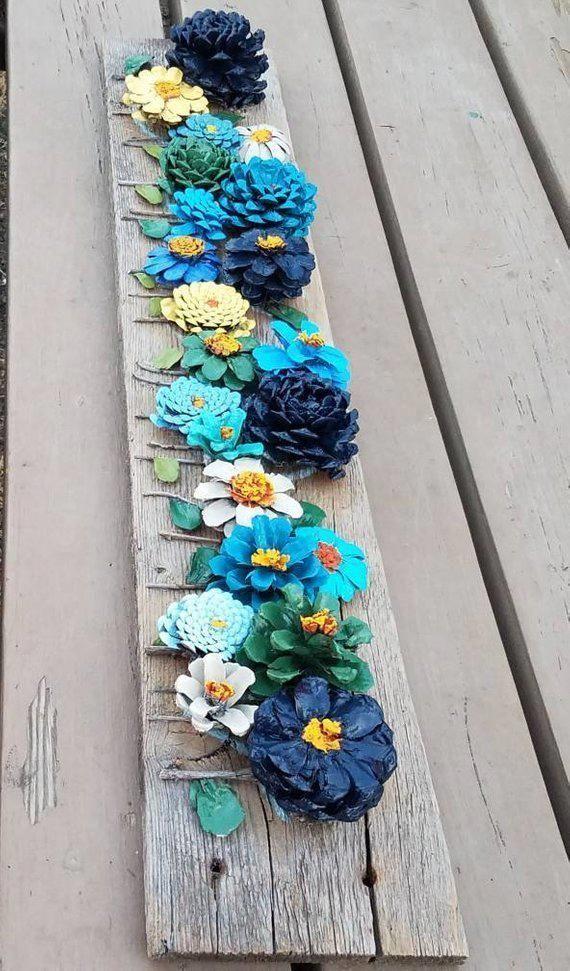 Handgemalte Tannenzapfenblumen auf hölzernem Wanddekor der Scheune