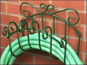 "Wrought-Iron Hose Hanger Our attractive scrolled hose hanger is hand made from wrought iron. It easily holds 200 feet of hose, and if you mount it up high you can store your hose in long loops that don't kink or twist when taken off the hanger again. Mounts on a wall using screws or lag bolts (not included) through the two small openings on the back. Durably protected with a polyester powder-coat paint. Measures 14"" x 7"" x 11"". Made in Canada."