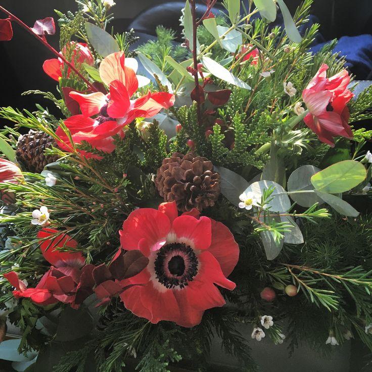 Centro de mesa con anémona roja, eucalipto, piña y follaje de temporada.