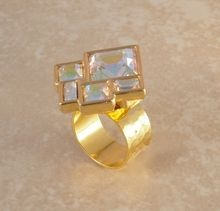 Square Crystal Ring. A fun, bold ring with a lot of sparkle. It is made with a vintage Swarovski piece. The crystals are AB coated, beveled,of different sizes and square shapes and set in gold tone metal. Size 1 1/4 inches. It is signed at the back with the Swarovski swan, which is now hidden under the ring pad. The ring band is hammered, gold plated and adjustable. The adjustment is hidden under the pad. Sizing small to 11.5.