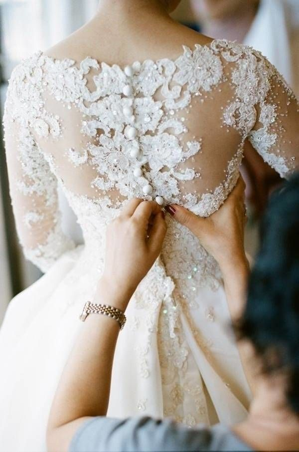 Your dress might have buttons, zippers, snaps or clasps. Whichever it is, make sure to get a close up photo of putting your dress on. It is the last finishing touch before you're ready to walk down the aisle.