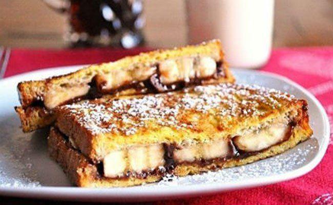 ΑΦΡΑΤΑ σαντουιτσάκια με σοκολάτα και μπανάνα!Υλικά 1/4 κούπας γάλα με 2% 2 μεγάλα αυγά, ελαφρά χτυπημένα 3/4κ.γ. εκχύλισμα βανίλιας 1/2κ.γ. ζάχαρη 1/8κ.γ. αλάτι 6 φέτες ψωμί για τοστ ολικής αλέσεως 4 1/2κ.σ. μερέντα 1 κούπα φέτες μπανάνας 2κ.γ. λάδι 1 1/2 κ.γ. ζάχαρη άχνη