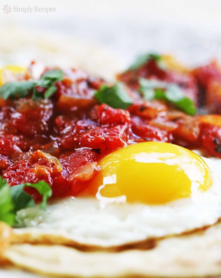 Huevos rancheros with fried eggs served on corn tortillas and smothered in cooked salsa. BEST Mexican breakfast ever! On SimplyRecipes.com