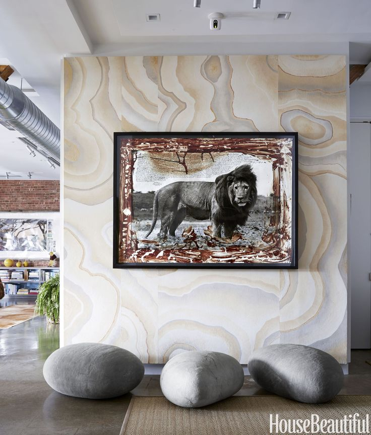 "A Peter Beard photograph hangs in the entry. The felt ""boulders"" are from VivaTerra, while the Sisal rug is by Stark.   - HouseBeautiful.com"