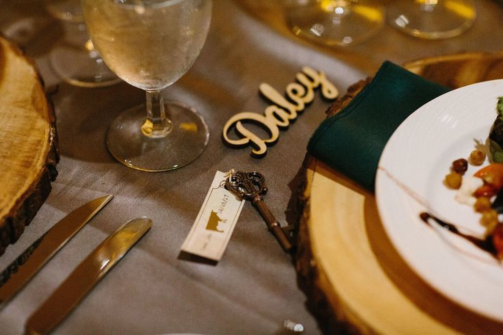 Natural Forrest Inspired Wedding Reception Table Decor with Natural Bark Edged Wooden Chargers, Forrest Green Napkins, Antique Key and Printed Paper Escort Card, and Laser Cut Wooden Name Card