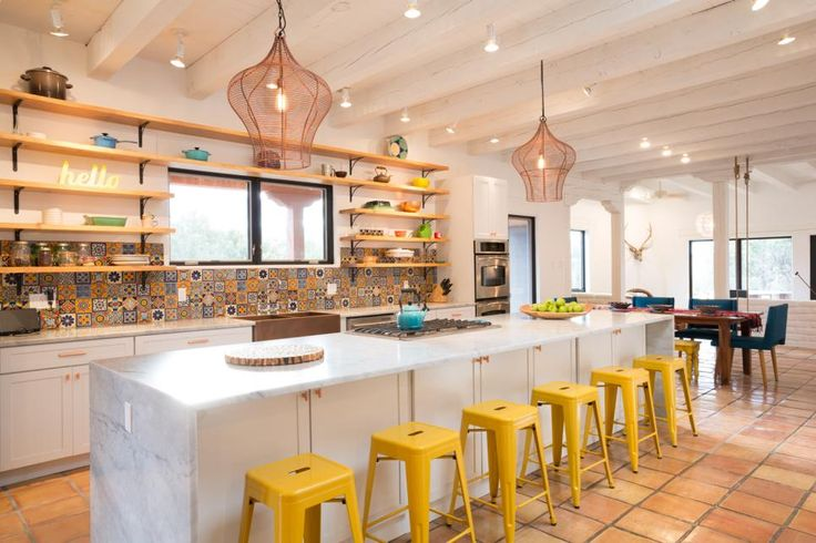 In this bright and happy kitchen, a long island provides space for six sunshine-yellow barstools, allowing the whole family to hang out while food is prepared. Mexican tile creates a fun and colorful backsplash, while open shelving adds decoration and keeps needed items at hand. The white backdrop allows accessories and fabrics to pop.