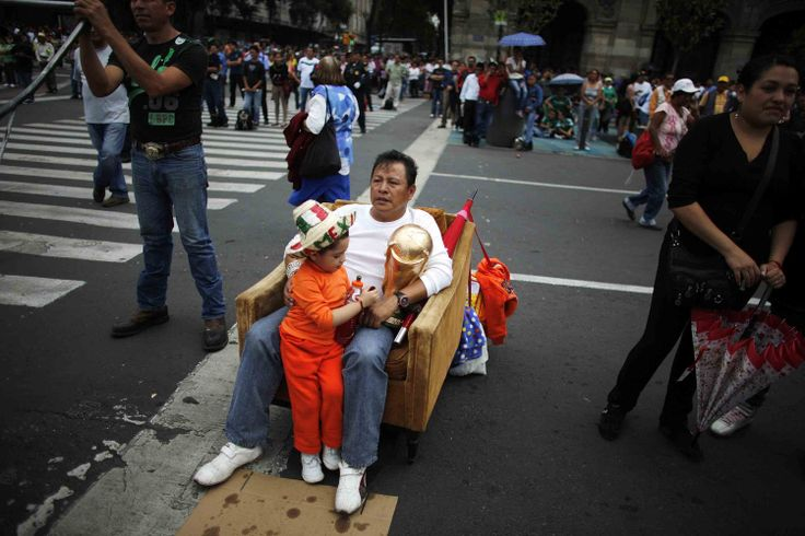 A father in downtown Mexico City moved a chair into the street to watch Mexico play Cameroon with his son.  Read more: http://www.businessinsider.com/photos-fans-watching-world-cup-2014-6#ixzz35L3t9Voc
