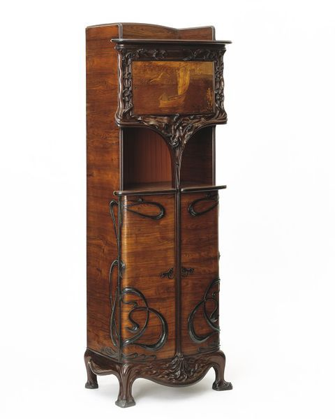>Louis Majorelle, Nancy, France       ca. 1900. Cabinet, Veneered in kingwood, with marquetry panel in birch, elm, oak, zebrano, rosewood, padouk and other woods, on an oak and possibly mahogany carcase, with wrought iron mounts; the low stand and framing to the upper sections in carved purpleheart.