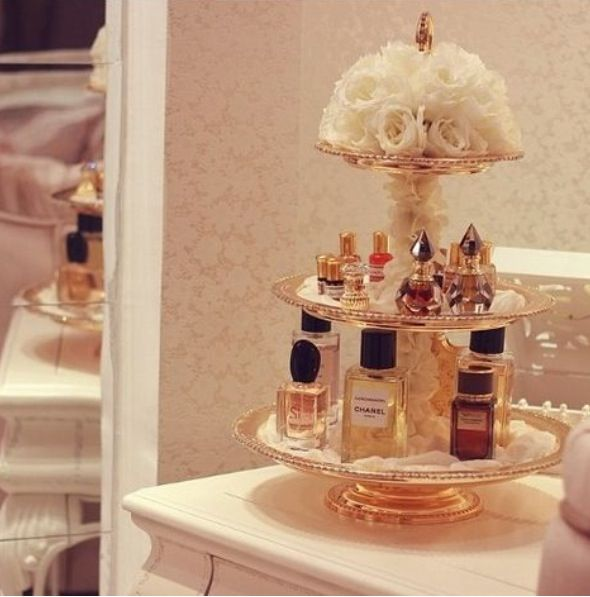 tiered perfume stand topped with flower arrangement