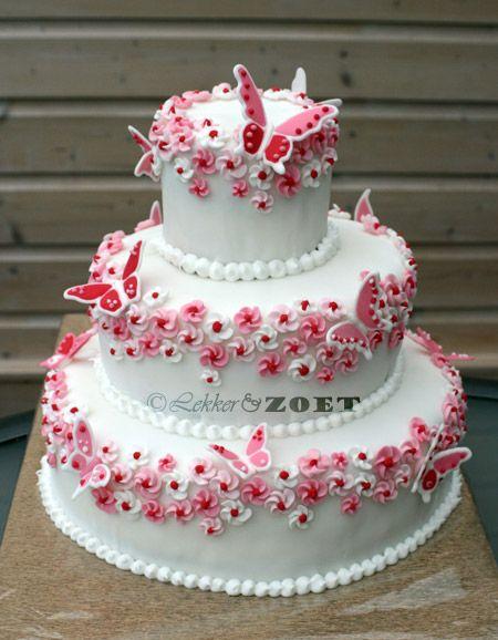 Witte bruidstaart met rood/roze bloemen en vlinders