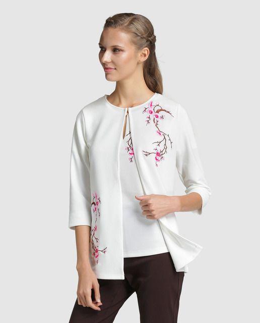 Chaqueta de punto en color blanco con bordado floral a contraste. Tiene manga francesa y escote redondo con cierre.