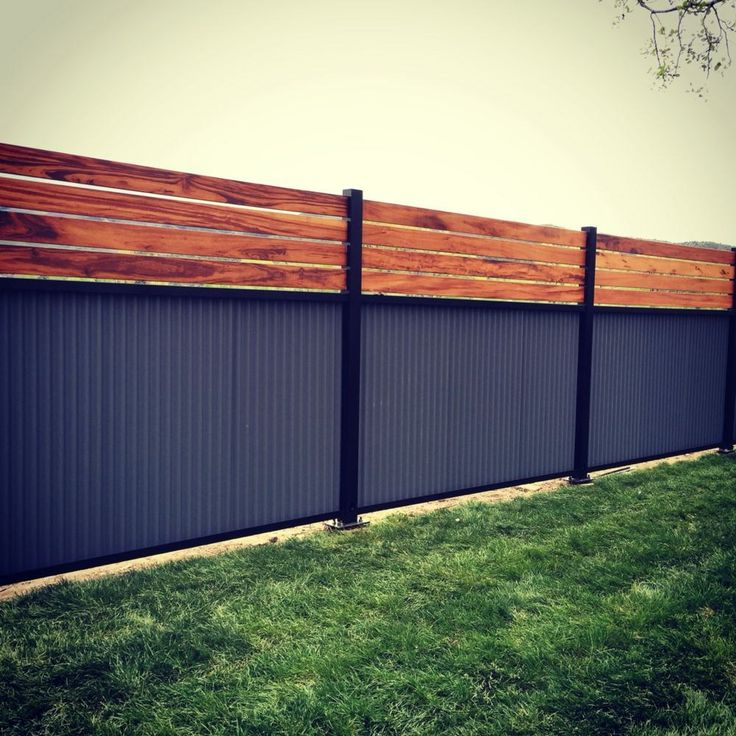 Dead link - just an image.  Custom privacy fence, built out of metal post, tiger wood, and corrugated metal.