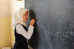 Girl writing on board in Iraq.