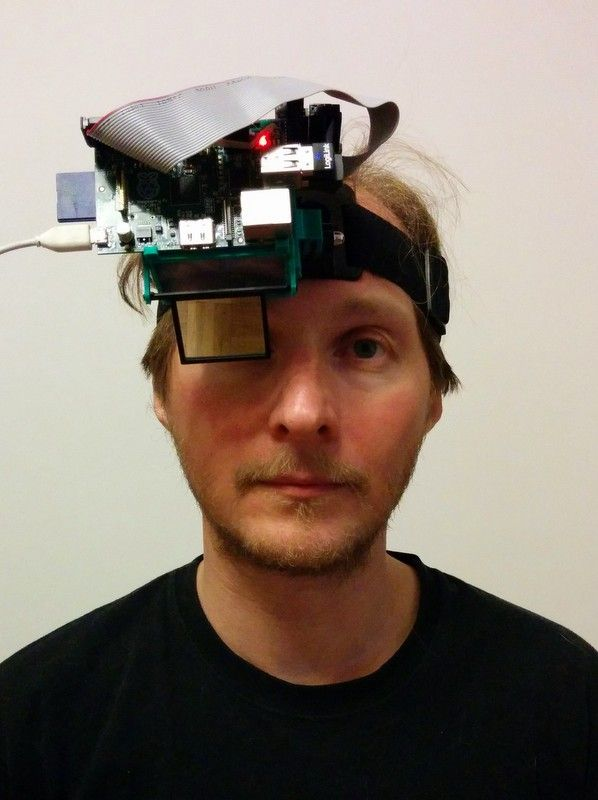 """I wanted to do something interesting with my RPi and a 2.4"""" TFT LCD. Google Glass was hot in the news, so I've decided to hack something similar. The semi-transparent mirror was extracted from Eye of Horus Beamsplitter, and the projection lens is cut from a plastic 3x Fresnel magnifying lens. The box and mounting parts are 3D-printed from ABS. Head strap is for GoPro. One RPi USB port is used for WiFi, and second for 2.4Ghz small wireless keyboard/mouse combo. All together cost around 100$…"""