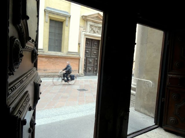 Peeping through the church doors in Parma, Italy
