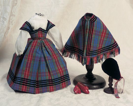 """French Scottish Costume To fit Huret style poupee,16""""–17"""" (40–43 cm). The Scottish style costume of richly woven linen/wool in vibrant blue,red and green colors comprises gown with box-pleated skirt below a fitted waist with detachable belt,and matching cape with self- fringe,each trimmed with narrow bands of black velvet ribbon,along with white chemisette with black velvet ribbon at neckline and cuffs. Included with the ensemble is a matching black velvet Scottish tam edged Circa 1860"""