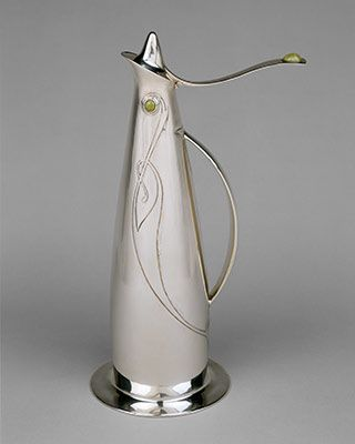 Though the jug superficially recalls the aesthetics of contemporary French Art Nouveau, the jug is uniquely British in drawing aesthetic inspiration from traditional Celtic designs. Its flat disk base effectively grounds the jug's sinuous decorative curves and remarkable flyaway thumbpiece. (Archibald Knox, 1901)