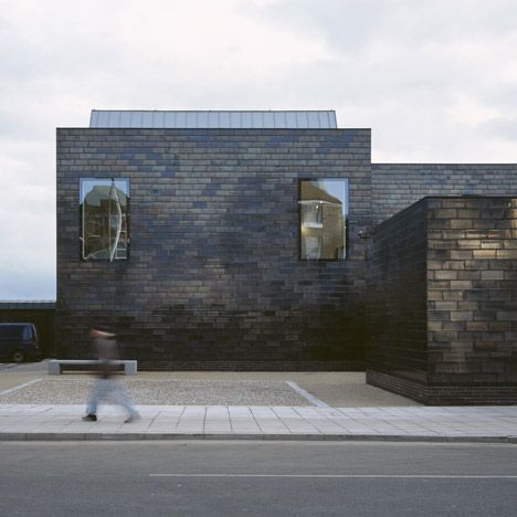 British architects HAT Projects --seaside gallery in Hastings, England, with a shimmering exterior of black glazed tiles.