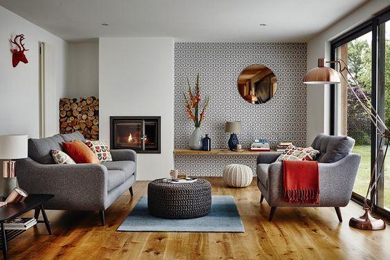 Przytulny salon z ciekawą tapetą w tle, oraz miedzianymi dodatkami.