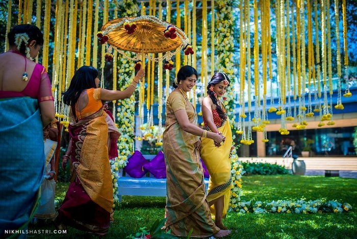 Bunts are a rather festive community  and when this particular Mangalorean wedding landed in our inboxes,  it gave it a whole lot of colour. The purple and yellow haldi decor, the adorable bride & groom chairs, the gorge outfits and the palanquin the bride made her entry in...ah -amazing! Major