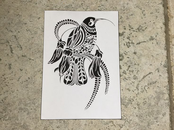 Paper cut of native New Zealand bird the Huia on a Kowhai branch.