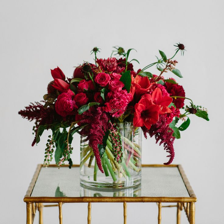 Red flower arrangement from Isari Flower Studio. Amaryllis and tulips. Photography by Shane and Lauren Photography.