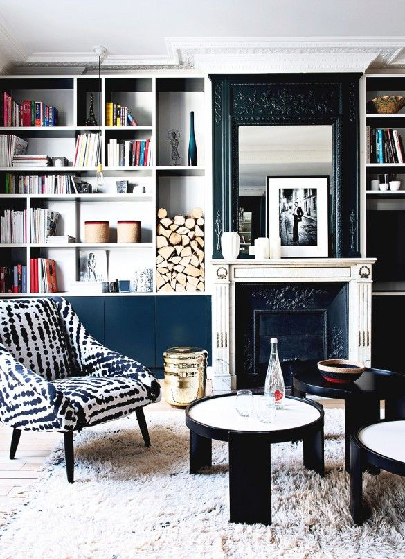This warm living room features large  black and white bookshelves, a fireplace with engraved mantel, a patterned armchair, and three circular coffee tables in varying heights.