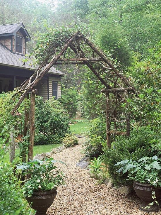 Love this garden entry..branches tied together, gravel path with trees, lush landscaping