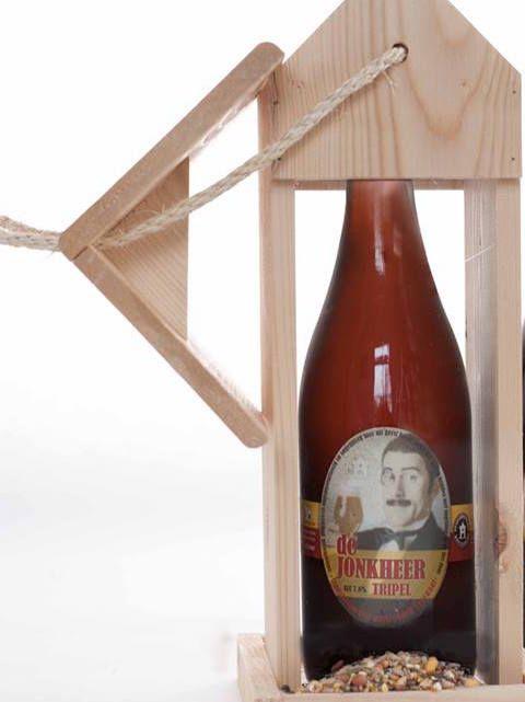 Een kerstpakket bestaande uit een vogelvoederhuis van duurzaam hout met een fles bier van 0,75 liter.